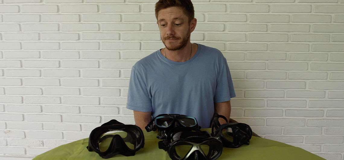 man in blue shirt looking at different snorkel masks