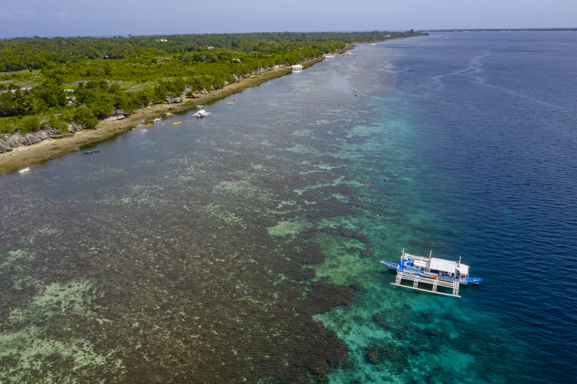 Aerial view of coral reef and local Philippine boat