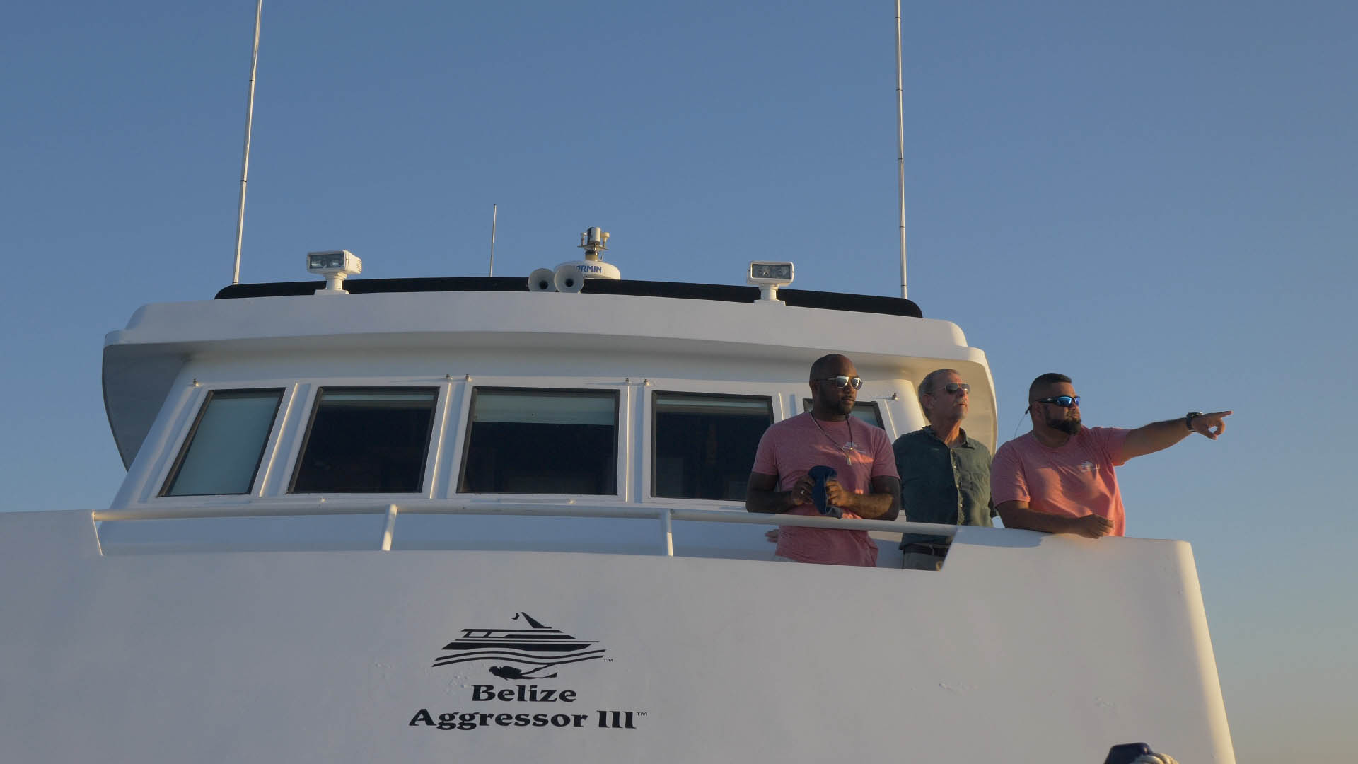 Captain and guests looking through binoculars