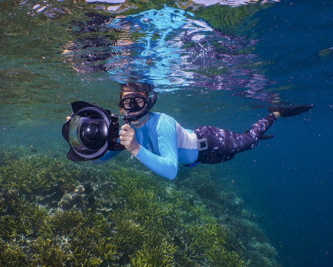 snorkeler with big underwater camera