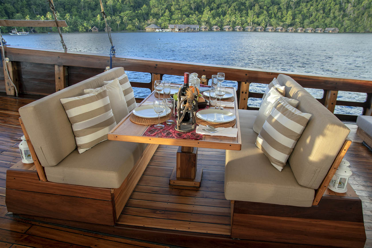 coralia liveaboard table setting with islands behind