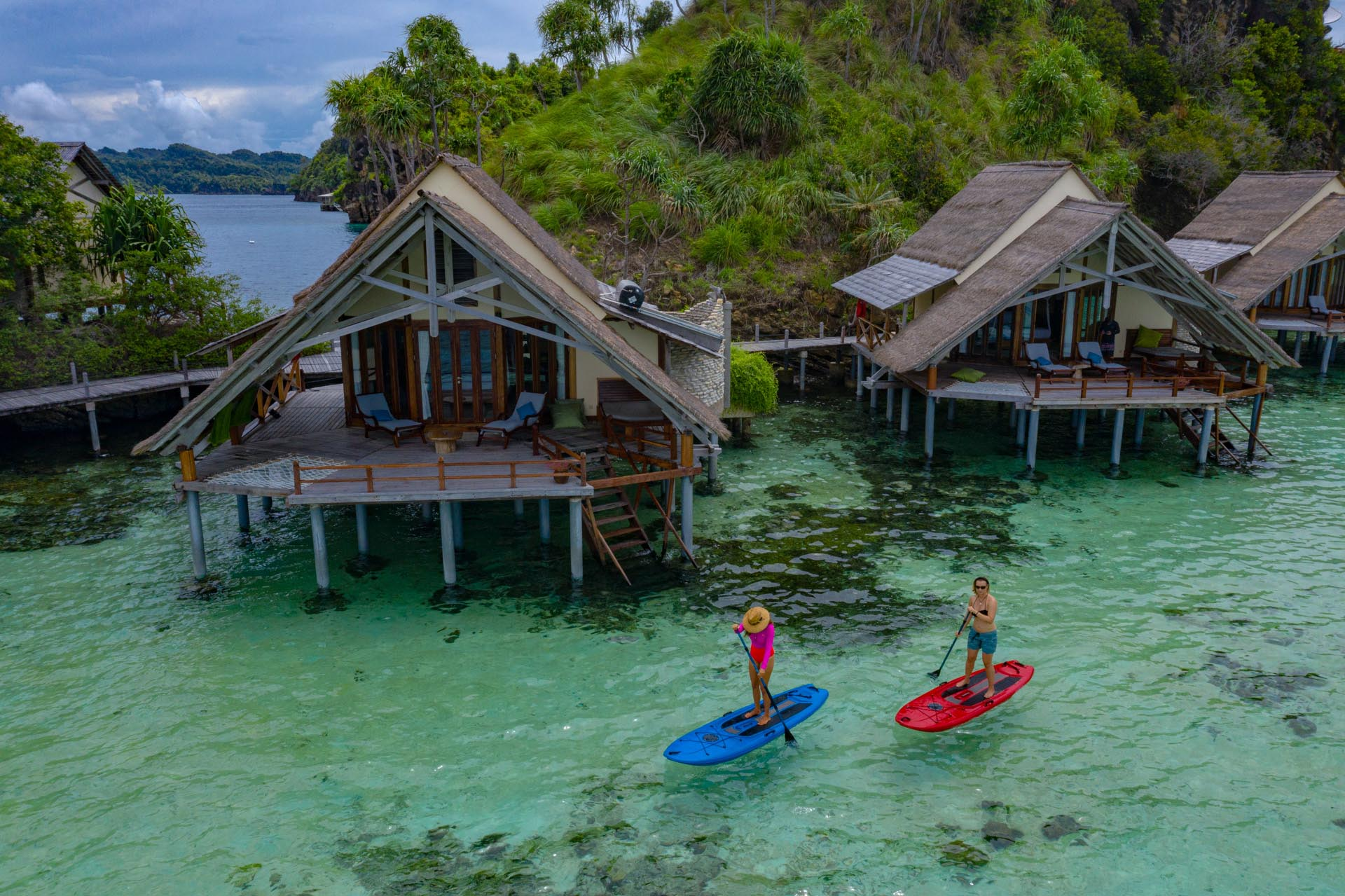 two paddle boarders infront of misool resort's bungalows