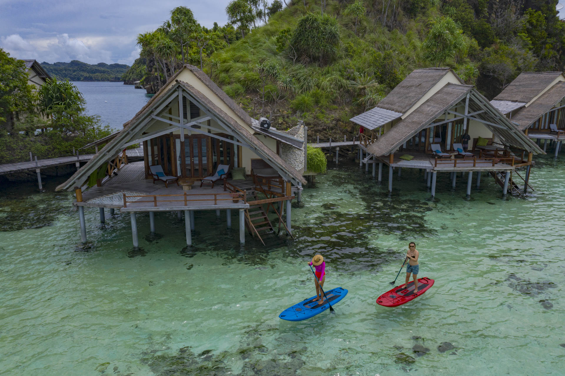 two girls paddleboarding in front of the water bungalows at misool resort