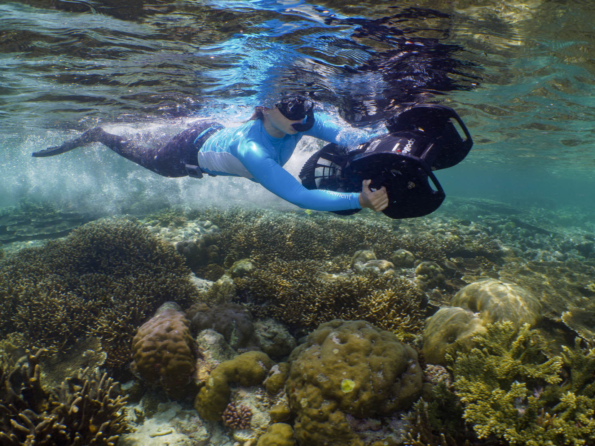 snorkeler riding an underwater scooter